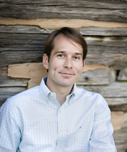 Author AG Riddle in a light blue shirt standing in front of rough wooden boards